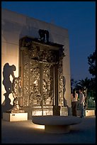 A couple contemplates Rodin's Gates of Hell at night. Stanford University, California, USA