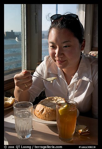 Woman eating a bown of clam chowder on the pier. Santa Cruz, California, USA (color)