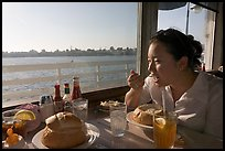 Woman eating clam chowder in a sourdough bread bowl. Santa Cruz, California, USA (color)