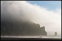 Two people strolling on the beach at the base of Morro Rock. Morro Bay, USA (color)
