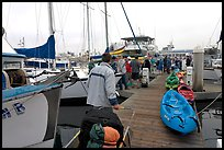 Pier with passengers preparing to board a tour boat with outdoor gear, Ventura. California, USA