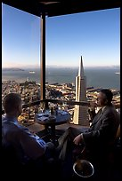 Businessmen with a bottle of Champagne in the Carnelian Room with panoramic view of the City. San Francisco, California, USA (color)