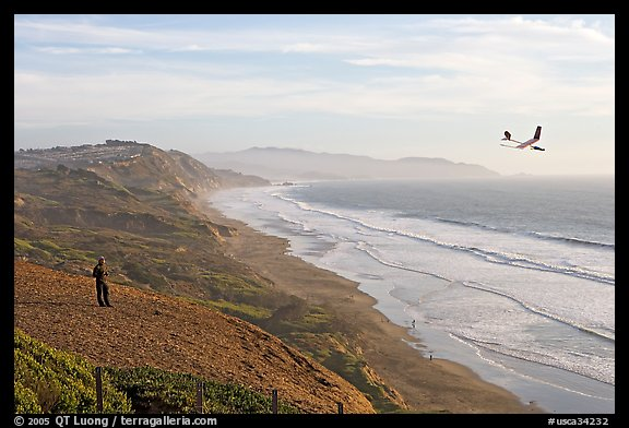 Man piloting model glider, Fort Funston, late afternoon. San Francisco, California, USA (color)