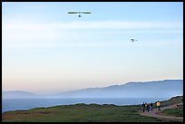 Hang gliders soaring above hikers, Fort Funston, late afternoon. San Francisco, California, USA ( color)