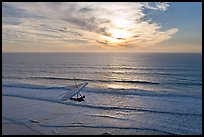 Hang glider flying  above ocean, Fort Funston, sunset. San Francisco, California, USA