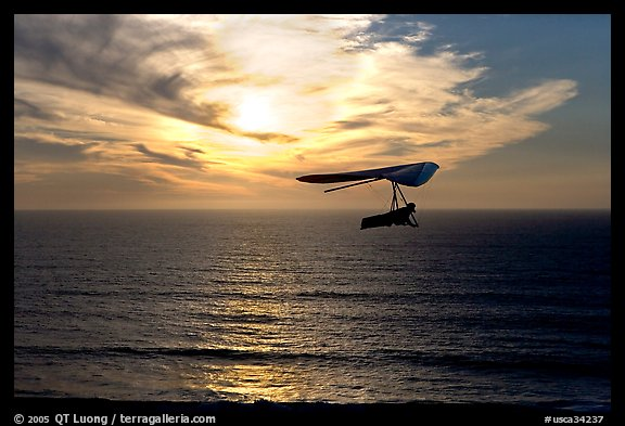 Soaring in a hang glider above the ocean at sunset,  Fort Funston. San Francisco, California, USA (color)