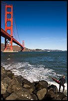 Surfer poised to jump in water below the Golden Gate Bridge. San Francisco, California, USA ( color)