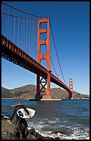 Surfer stepping on rocks and Golden Gate Bridge. San Francisco, California, USA