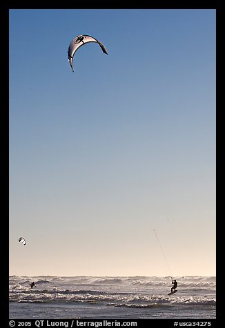 Kite surfing in Pacific Ocean waves, late afternoon. San Francisco, California, USA (color)
