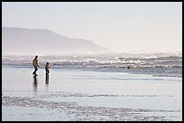 Man and child on wet beach, afternoon. San Francisco, California, USA (color)