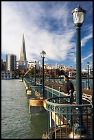 Visitor standing on pier 7, morning. San Francisco, California, USA