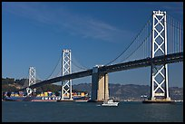 Cargo ship passing below the Bay Bridge. San Francisco, California, USA (color)