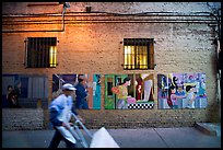 Man pushing a cart in front of mural paintings, Ross Alley, Chinatown. San Francisco, California, USA