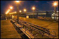Benches and lights on Pier 7 with Bay Bridge in background, evening. San Francisco, California, USA