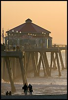 Beachgoers, surfers in waves,  and Huntington Pier. Huntington Beach, Orange County, California, USA