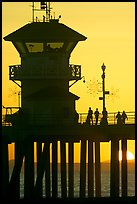 People and pier silhouetted by the setting sun. Huntington Beach, Orange County, California, USA (color)