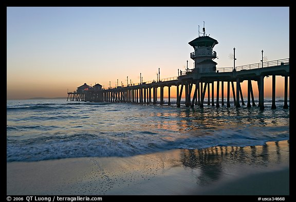 Huntington Pier reflected in wet sand at sunset. Huntington Beach, Orange County, California, USA (color)