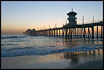 Huntington Pier reflected in wet sand at sunset. Huntington Beach, Orange County, California, USA ( color)