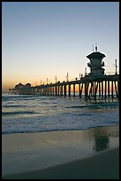 Huntington Pier and reflections in wet sand at sunset. Huntington Beach, Orange County, California, USA (color)