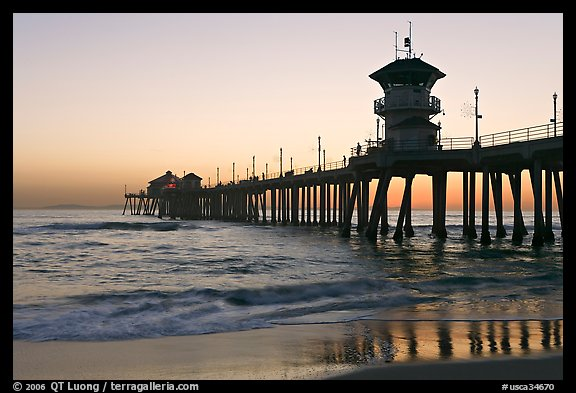 The 1853 ft Huntington Pier reflected in wet sand at sunset. Huntington Beach, Orange County, California, USA (color)