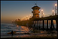 Surfer and Huntington Pier lights at twilight. Huntington Beach, Orange County, California, USA