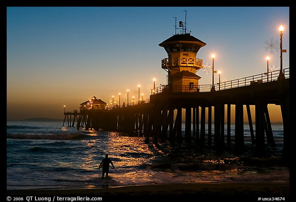 Surfer entering water next to the Huntington Pier, sunset. Huntington Beach, Orange County, California, USA