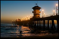 Surfer entering water next to the Huntington Pier, sunset. Huntington Beach, Orange County, California, USA (color)