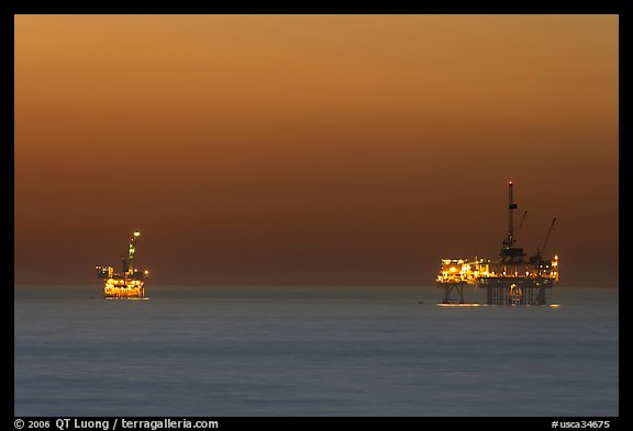 Oil drilling platforms lighted at dusk. Huntington Beach, Orange County, California, USA