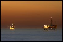 Oil drilling platforms lighted at dusk. Huntington Beach, Orange County, California, USA ( color)