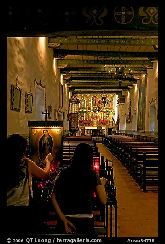 Two women light up candles in the Serra Chapel. San Juan Capistrano, Orange County, California, USA