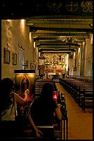 Two women light up candles in the Serra Chapel. San Juan Capistrano, Orange County, California, USA (color)
