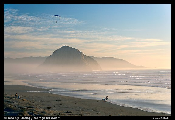 Motorized paraglider, women walking dog, with Morro Rock in the distance. Morro Bay, USA
