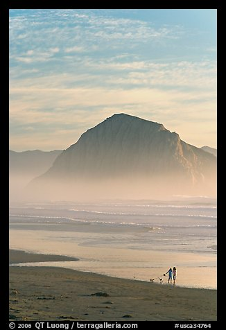 Women walking dog on the beach, with Morro Rock behind. Morro Bay, USA (color)