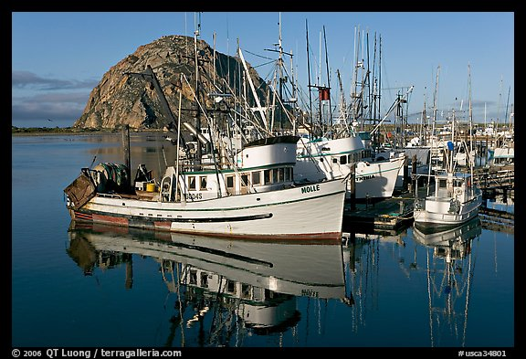 Fishing boats with reflections and Morro Rock, early morning. Morro Bay, USA