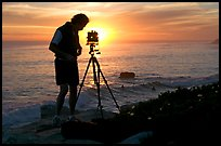 Photographer and large format camera on tripod at sunset. Santa Cruz, California, USA
