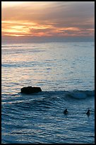 Surfers and rock at sunset. Santa Cruz, California, USA