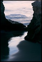Reflection on wet sand through rock opening, Natural Bridges State Park, dusk. Santa Cruz, California, USA (color)