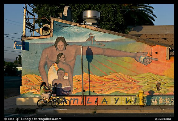 Hispanic girl on bicycle and mural, Alviso. San Jose, California, USA