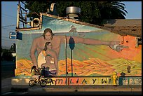 Hispanic girl on bicycle and mural, Alviso. San Jose, California, USA (color)