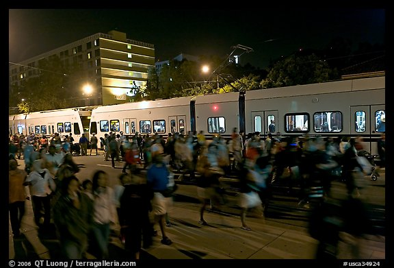 Crowds and light rail on San Carlos Avenue at night, Independence Day. San Jose, California, USA (color)