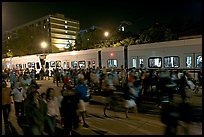 Crowds and light rail on San Carlos Avenue at night, Independence Day. San Jose, California, USA