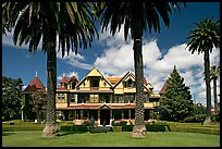 Palm trees and mansion facade. Winchester Mystery House, San Jose, California, USA