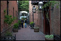 Couple walking in an alley of brick walls, San Pedro Square. San Jose, California, USA ( color)
