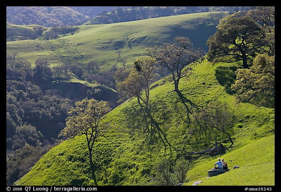 Couple sitting on hillside in early spring, Sunol Regional Park. California, USA