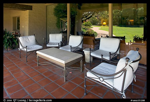 Chairs and coffee table on porch, Sunset gardens reflected. Menlo Park,  California, USA (color)