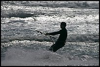 Kitesurfer silhouette against silvery water, Waddell Creek Beach. California, USA
