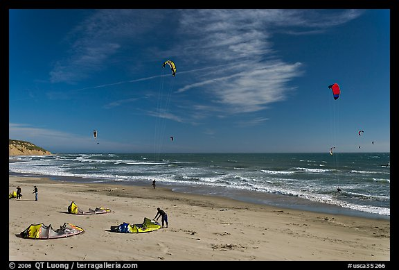 Kitesurfers rolling out sails on on beach, Waddell Creek Beach. California, USA