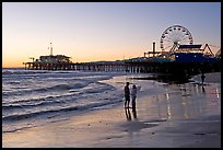 Couple on beach, with pier in the background, sunset. Santa Monica, Los Angeles, California, USA