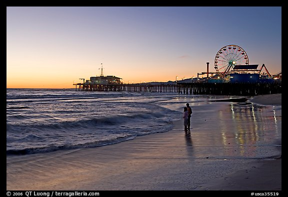Couple reflected in wet sand at sunset, with pier and Ferris Wheel behind. Santa Monica, Los Angeles, California, USA (color)