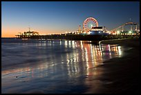 Pier and Ferris Wheel reflected on beach at dusk. Santa Monica, Los Angeles, California, USA